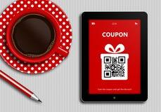 Tablet met kortingscoupon en kop van koffie die op tableclo liggen Stock Foto's