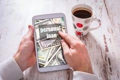 Tablet met persoonlijke lening in handen en zwarte koffie op houten lijst Royalty-vrije Stock Foto's