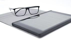Tablet met vage teksten en glazen royalty-vrije stock afbeeldingen