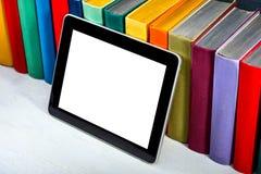 Tablet mit bunten Büchern auf Hintergrund lizenzfreie stockfotografie