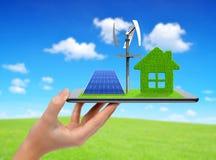 Tablet mit grünem Haus, Windkraftanlage und Sonnenkollektor Stockbild