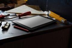 Tablet mit leerem Bildschirm auf einem dunklen Schrank mit Werkzeugen in einem schmutzigen Keller Lizenzfreies Stockfoto