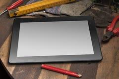 Tablet mit leerem Bildschirm in einer Werkzeug-Halle Stockfoto