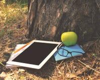Tablet mit leerem Bildschirm, Notizbücher, Apfel, Bleistift unter einem Baum Lizenzfreies Stockfoto