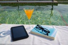 Tablet mit leerem Schirm, einem Glas Orangensaft und blauem Buch mit Gläsern auf dem weißen Tuch Lizenzfreies Stockfoto