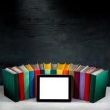 Tablet mit leerem Schirm mit bunten Büchern auf Hintergrund mit lizenzfreie stockfotos