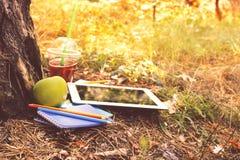 Tablet mit Notizbüchern, Bleistiften, grünem Apfel und Saft am Park Stockfotografie