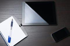 Tablet mit Notizbuch und Stift auf dunkler Tabelle Lizenzfreies Stockbild
