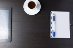 Tablet mit Notizbuch und Stift auf dunkler Tabelle Stockbilder