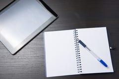 Tablet mit Notizbuch und Stift auf dunkler Tabelle stockfotos