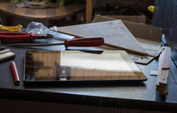 Tablet mit Reflexion auf einem dunklen Schrank mit Werkzeugen Lizenzfreie Stockfotografie