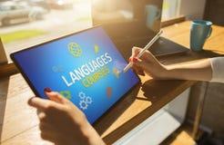 Tablet mit Sprachkursen simsen und Ikonen auf Schirm Englisch, das online lernt getrennte alte Bücher stockbild