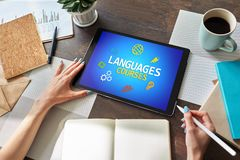 Tablet mit Sprachkursen simsen und Ikonen auf Schirm Englisch, das online lernt getrennte alte Bücher stockfotografie