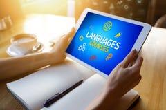 Tablet mit Sprachkursen simsen und Ikonen auf Schirm Englisch, das online lernt getrennte alte Bücher lizenzfreie stockfotos