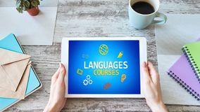 Tablet mit Sprachkursen simsen und Ikonen auf Schirm Englisch, das online lernt getrennte alte Bücher stockfoto