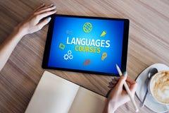 Tablet mit Sprachkursen simsen und Ikonen auf Schirm Englisch, das online lernt getrennte alte Bücher stockbilder