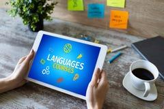 Tablet mit Sprachkursen simsen und Ikonen auf Schirm Englisch, das online lernt getrennte alte B?cher stockfotografie