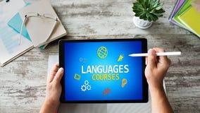Tablet mit Sprachkursen simsen und Ikonen auf Schirm Englisch, das online lernt getrennte alte B?cher lizenzfreies stockbild