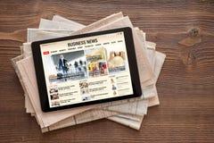 Tablet mit Wirtschaftsnachrichtwebsite auf Stapel Zeitungen Aller Inhalt wird gebildet stockbilder