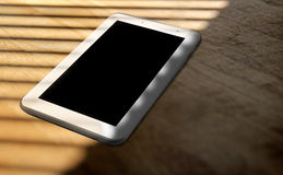 Tablet mobile device on shaded table Stock Photos