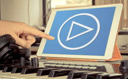 Tablet music producer touching application. Music and Video Play button on tablet in Music studio Royalty Free Stock Images