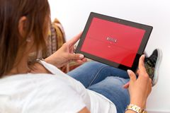 Tablet with netflix loading screen. Young woman. stock image