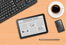 Tablet with news and office supplies laying on the Royalty Free Stock Image