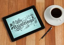 Tablet next to coffee showing black business doodles against blue background Stock Images