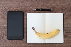 Tablet, notebook, pen and a banana on a wooden table. Image concept for journalism, liar and fake news, problems of hoaxes and tr. Uthfulness of the sources royalty free stock photo