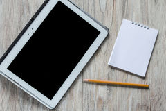 Tablet, notebook and pencil on wooden background Royalty Free Stock Photography