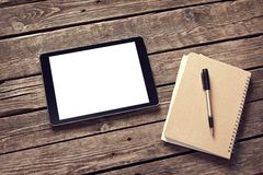 Tablet and notepad on desktop Royalty Free Stock Images