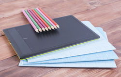 Tablet, Notizbuch und Bleistifte, die auf einem hölzernen Hintergrund liegen Stockbild