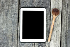 Tablet op houten oppervlakte en houten lepel Stock Afbeeldingen