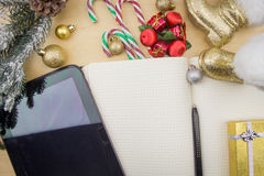 Tablet and open notebook with festive ornaments. Royalty Free Stock Photos