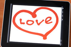 Tablet with a painted heart Royalty Free Stock Photography