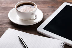 Tablet, paper notebook and coffee on the table Royalty Free Stock Photo