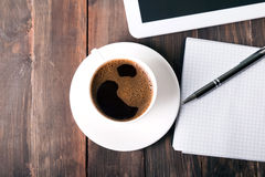 Tablet, paper notebook and coffee on the table Stock Image