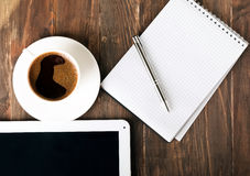 Tablet, paper notebook and coffee on the table Royalty Free Stock Image