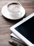 Tablet, paper notebook and coffee on the table Royalty Free Stock Photography