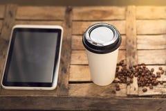 Tablet, Papierschale mit Kaffee und Kaffeebohnen auf einem hölzernen backg Lizenzfreie Stockfotografie