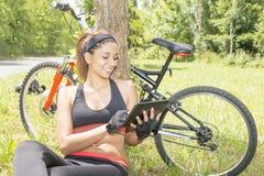 Tablet pc atlético de sorriso do portátil da mulher após o exercício, foto de stock