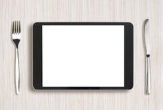 Tablet-PC auf hellem Holztisch mit Gabel und Stockbilder