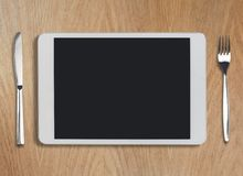 Tablet-PC auf Holztisch mit Gabel und Messer Stockfotografie