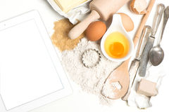 Tablet pc and baking ingredients eggs, flour, sugar, butter, yea Stock Photography