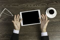 Tablet pc with blank screen in hands. Top view of businessman sitting at table with tablet pc in hands Stock Photography