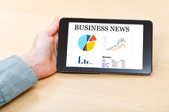 Tablet PC with business news on screen at desk Royalty Free Stock Images