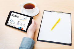 Tablet PC with business news on screen at table Stock Photo
