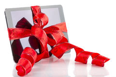 Tablet pc with christmas red ribbon Royalty Free Stock Photos