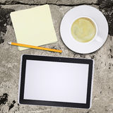 Tablet pc and coffee cup on old concrete surface Stock Photography