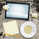 Tablet pc and coffee cup on old concrete surface Royalty Free Stock Image